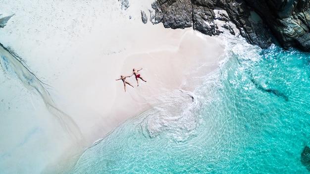 Spiaggia drone vista isola tropicale, spiaggia bianca con onde, coppia sdraiata sulla spiaggia