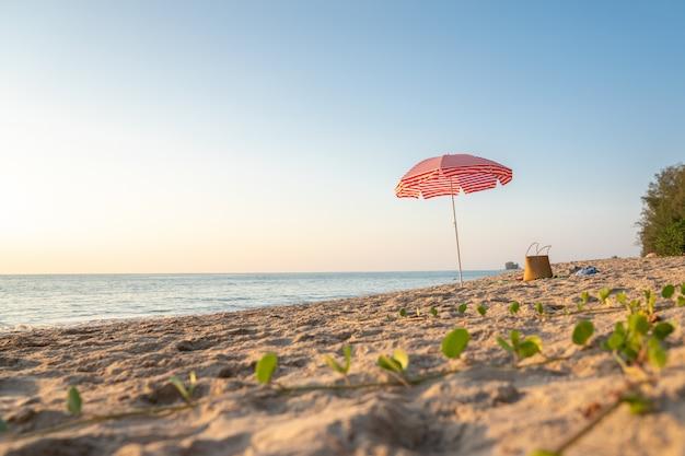 Spiaggia estiva e ombrellone rosso per il concetto di vacanza
