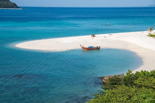Spiaggia karma con barca a coda lunga nel mare tropicale sull'isola di lipe