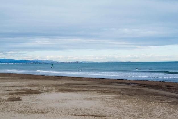 Spiaggia nuvolosa con onde del mare. windsurf nel mar mediterraneo sulla spiaggia di valencia. spiaggia vuota di primavera.