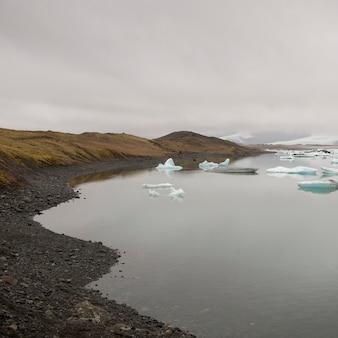 Spiaggia rocciosa sul lago glaciale con iceberg galleggianti