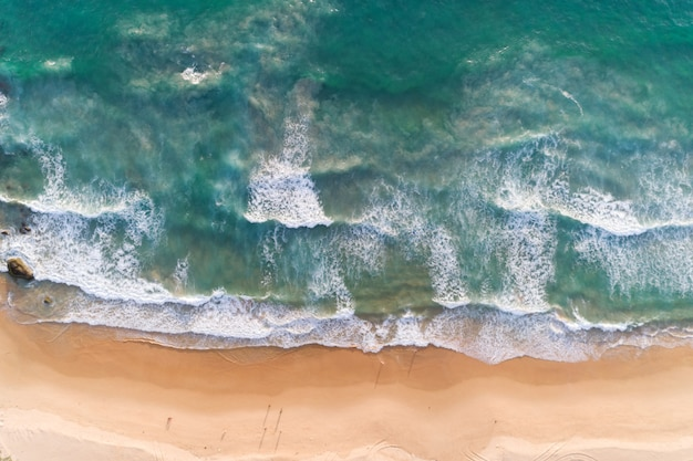 Spiaggia sabbiosa di vista aerea e onde che si infrangono sulla riva sabbiosa
