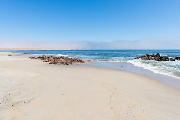 Spiaggia sabbiosa e costa sull'oceano atlantico a cape cross, namibia, famosa per la vicina colonia di foche. cielo blu chiaro.