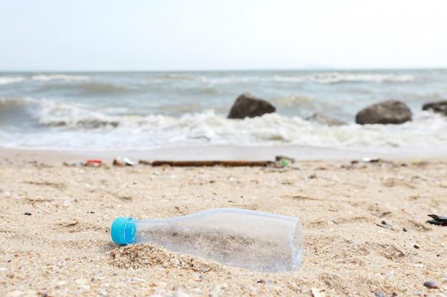 Spiaggia sporca piena di inquinamento di plastica, immondizia e rifiuti sabbiosi
