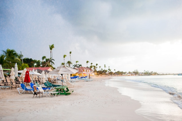 Spiaggia tropicale caraibica idilliaca con sabbia bianca, acqua dell'oceano turchese prima della pioggia