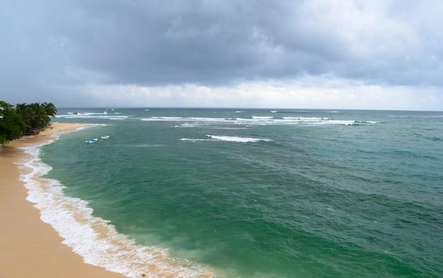 Spiaggia tropicale di tramonto epico nello sri lanka, nuvole drammatiche di monsone del cielo