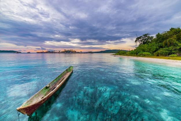 Spiaggia tropicale, mar dei caraibi, canoa che galleggia sull'acqua del turchese, isole togean a distanza, indonesia