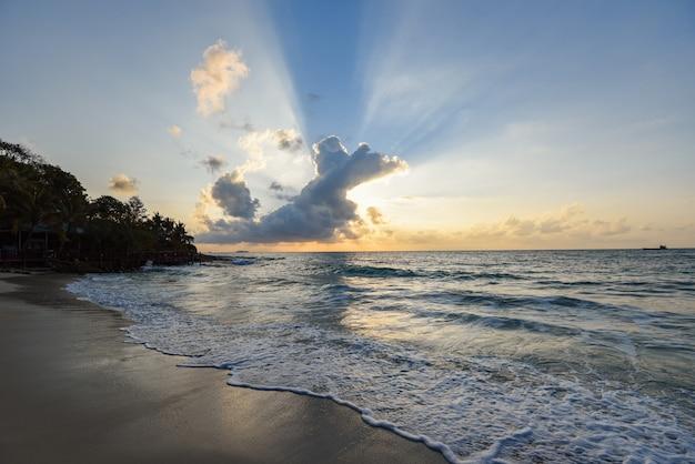 Spiaggia tropicale sabbiosa stupefacente con la siluetta della spiaggia tropicale - cielo drammatico del mare di alba o di tramonto