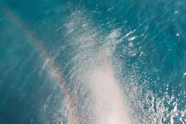 Spiaggia, viaggi e ambiente. arcobaleno su sfondo blu oceano. struttura della superficie dell'acqua dell'oceano, fondo d'annata di estate.