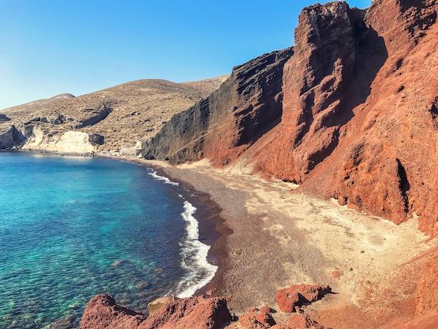 Spiaggia vulcanica rossa a santorini, in grecia. acque azzurre del mar mediterraneo.