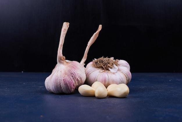 Spicchi d'aglio interi e pelati sul nero.