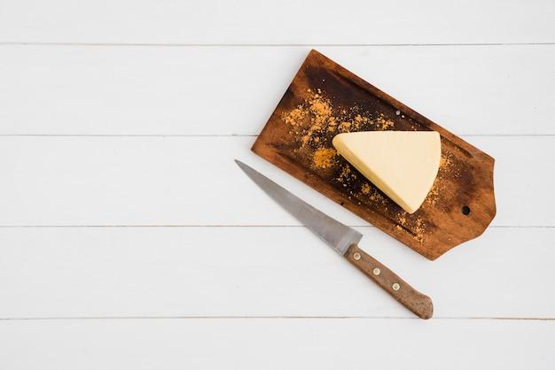 Spicchi di formaggio spolverati di spezie sul tagliere con un coltello affilato sopra il tavolo bianco