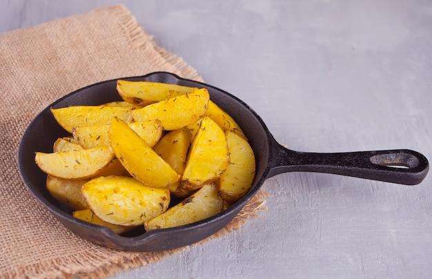 Spicchi di patate al forno fatti in casa con erbe sulla pentola di ferro nero su sfondo grigio