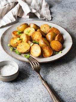 Spicchi di patate arrostiti fritti con scalogno su piastra vintage su una superficie grigia