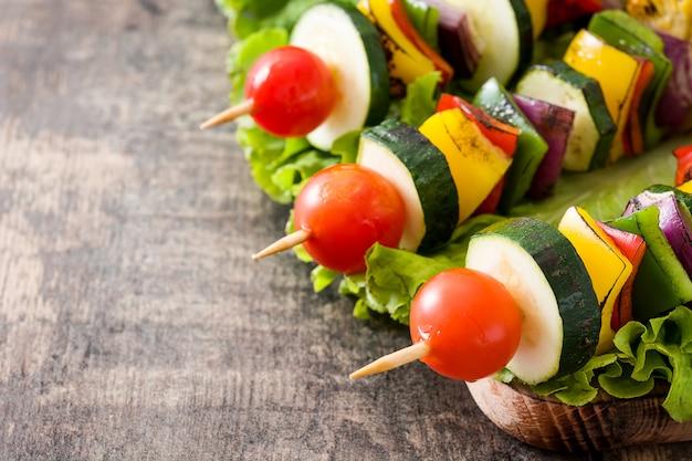 Spiedi di verdure sulla fine di legno della tavola su