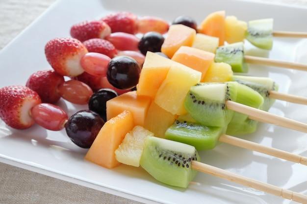 Spiedi freschi della frutta dell'arcobaleno sul piatto bianco
