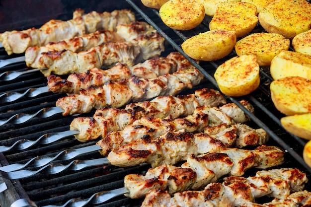 Spiedini alla griglia con patate e carne e kebab vengono arrostiti sulla griglia