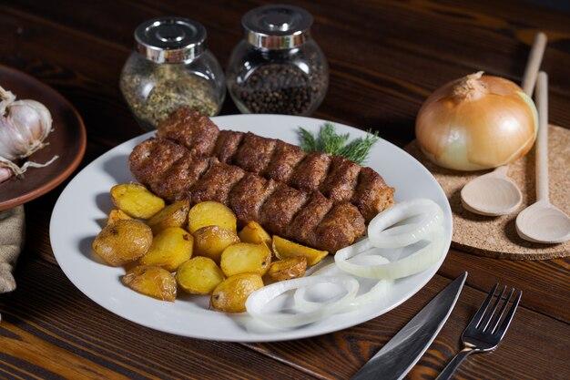 Spiedini alla griglia sul piatto a base di pollo, pancetta e verdure