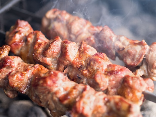 Spiedini di carne alla griglia alla brace, con fumo. il cibo di strada.