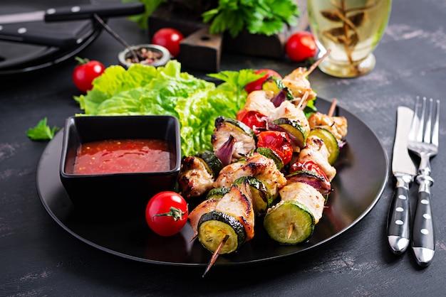 Spiedini di carne alla griglia, shish kebab di pollo con zucchine, pomodori e cipolle rosse