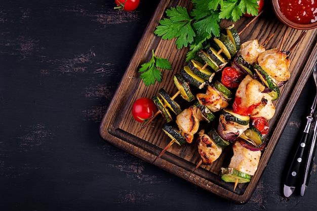 Spiedini di carne alla griglia, spiedini di pollo con zucchine, pomodori e cipolle rosse