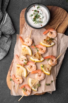 Spiedini di gamberetti di pesce fresco su tavola di legno
