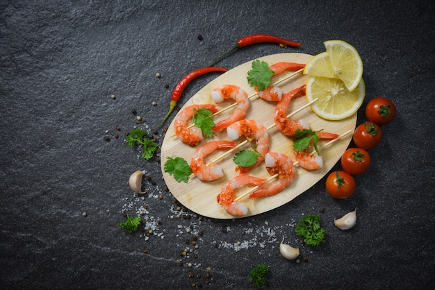 Spiedini di gamberetti gamberetti a base di pesce cucinati con erbe aromatiche e spezie su legno