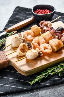 Spiedini di legno con frutti di mare alla griglia, gamberi, polpi, calamari e cozze. sfondo grigio. vista dall'alto