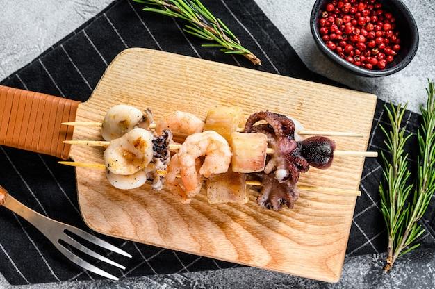 Spiedini di legno con frutti di mare alla griglia, gamberi, polpi, calamari e cozze.