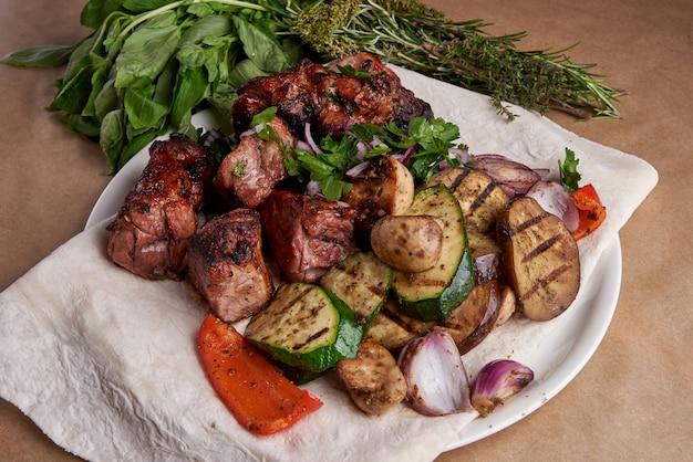 Spiedini di maiale, carne barbecue sul piatto e verdure grigliate