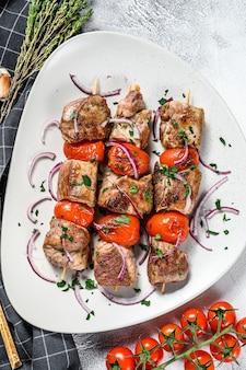 Spiedini di maiale su spiedini con pomodoro e pepe