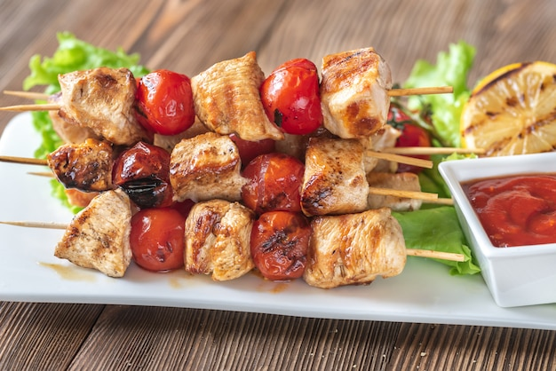 Spiedini di pollo alla griglia sul piatto bianco