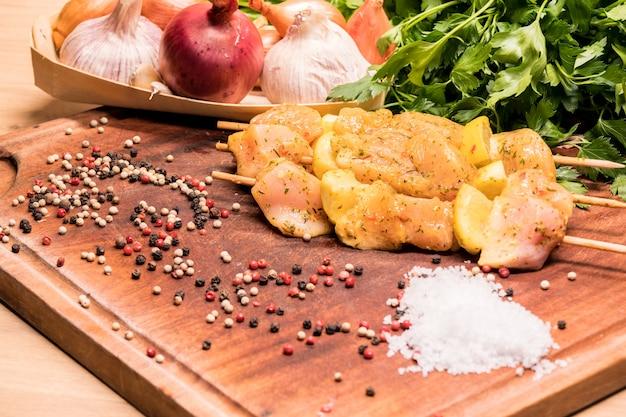 Spiedini di pollo crudo marinati con limone su una tavola di legno
