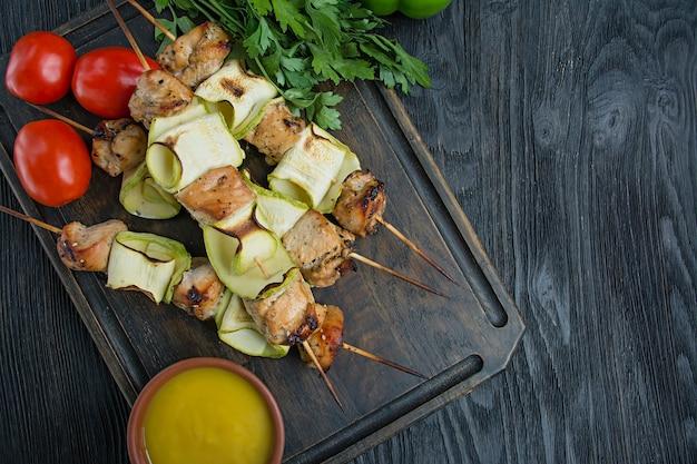 Spiedini su uno spiedino con zucchine con salsa, verdure ed erbe su un tagliere.