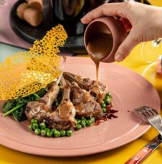 Spiedino di costolette di agnello guarnito con salsa barbecue, con piselli e spinaci