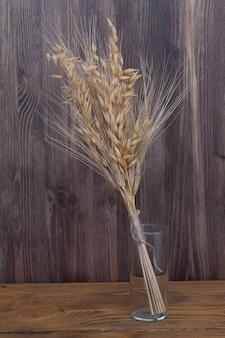 Spighe di grano e orzo in un vaso di vetro sullo sfondo di tavole di legno.