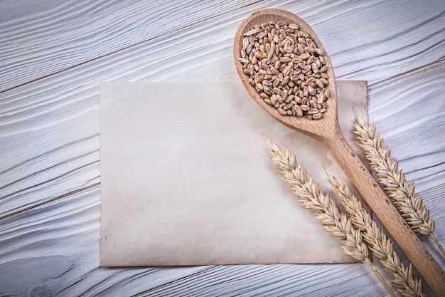 Spighe di segale di grano maturo, grani in cucchiaio di legno e foglio di carta vintage sul bordo di legno