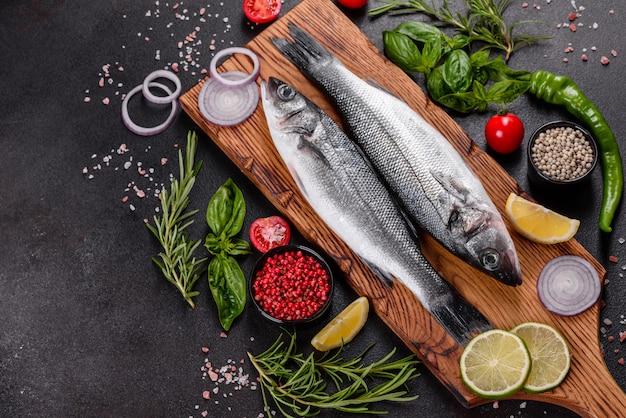 Spigola di pesce fresco e ingredienti per cucinare. branzino crudo di pesce