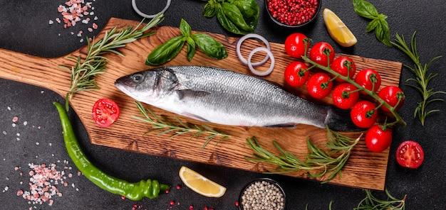 Spigola di pesce fresco e ingredienti per cucinare. branzino di pesce crudo con spezie ed erbe aromatiche su un tavolo scuro