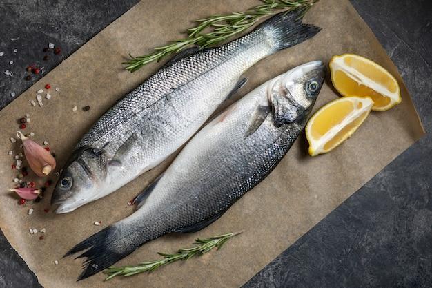 Spigola di pesce fresco e ingredienti per cucinare, limone e rosmarino. vista dall'alto di sfondo scuro.