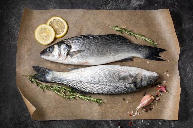 Spigola di pesce fresco e ingredienti per cucinare, limone e rosmarino