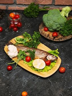 Spigola di pesce fresco e ingredienti per cucinare. spigola di pesce crudo con spezie ed erbe sulla tavola di ardesia nera. vista dall'alto.