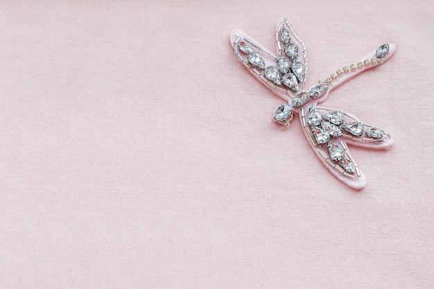 Spilla libellula di strass e perline su fondo di tessuto rosa