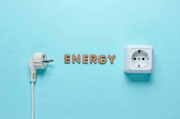 Spina e presa di corrente con la parola energia sulla superficie blu.