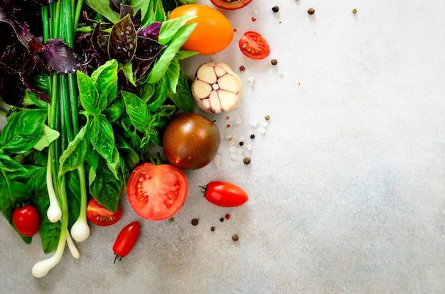 Spinaci freschi, cipolla verde, basilico, erbe, aneto e pomodori su fondo concreto grigio, fuoco selettivo.