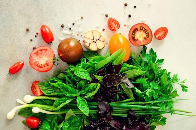 Spinaci freschi, cipolla verde, basilico, erbe aromatiche, aneto e pomodori. ingredienti per cucinare vegano, crudo, concetto di disintossicazione
