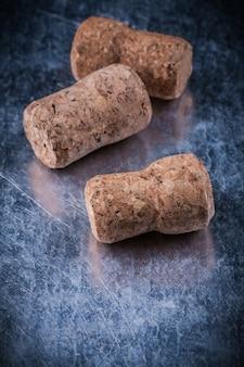 Spine del sughero di champagne sul concetto metallico dell'alimento e della bevanda del fondo