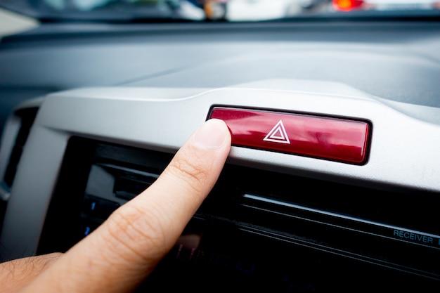 Spingendo il pulsante di emergenza per il pericolo di luci rosse su una console dell'auto