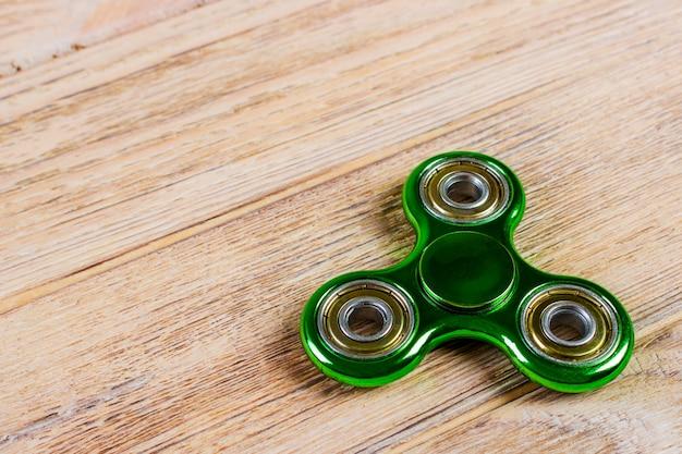 Spinner verde di fidget su un legno