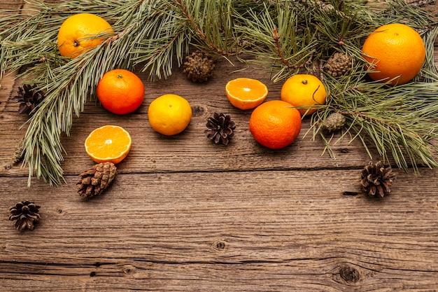 Spirito di natale sul tavolo di legno. arance fresche, mandarini, rami di pino e coni. decorazioni naturali, tavole di legno vintage